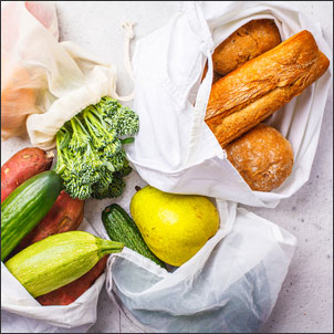 Vegetables and bread in reusable bags